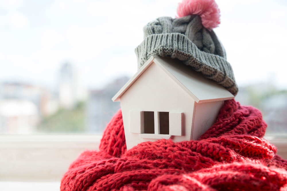 Toy house wrapped in scarf and beanie