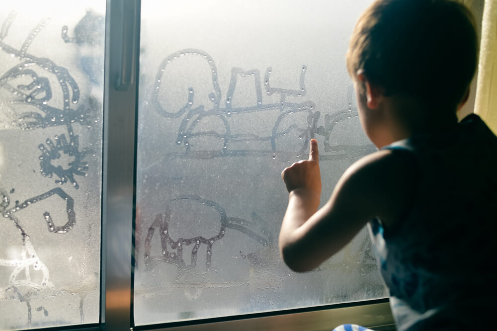 Boy drawing on a window with condensation.
