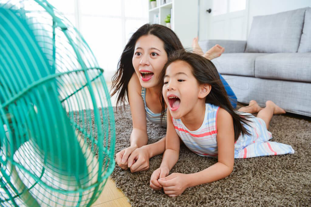 mother and daughter in front of fan