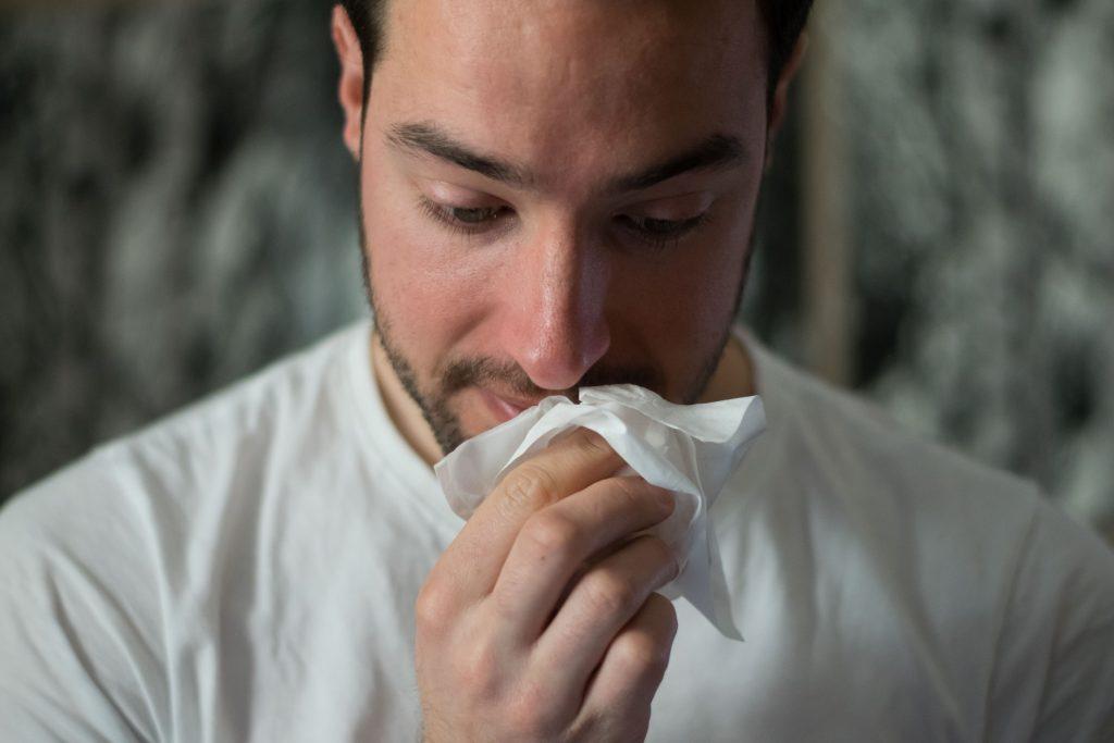 man wiping nose